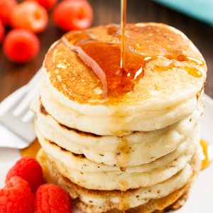 A sweet stack of buttermilk pancakes piled high and syrup being poured over top