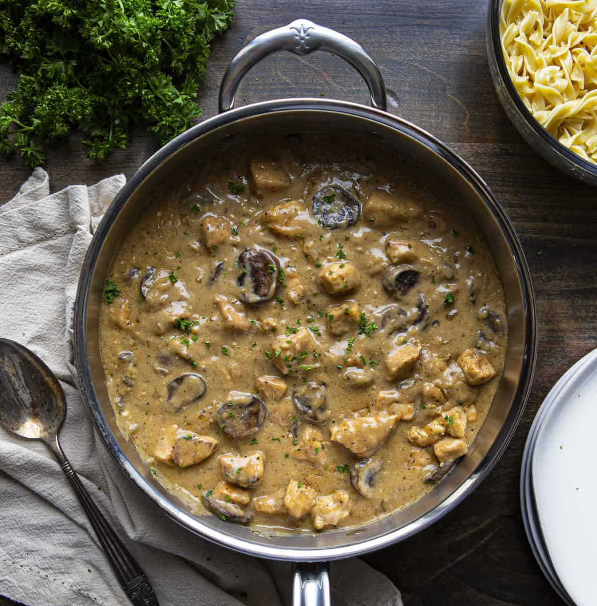 Overhead of skillet of Chicken Stroganoff Recipe with noodles, parsley, and plates by it