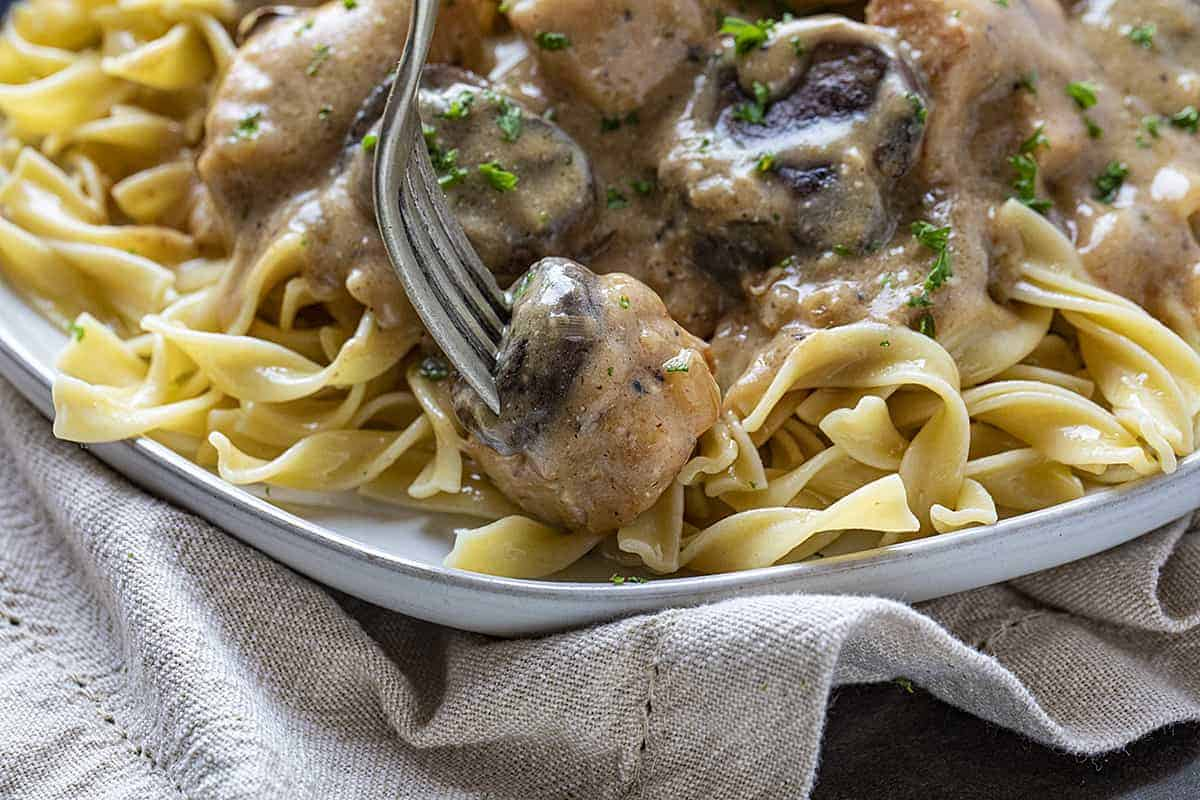 Fork Picking Piece of Chicken and Mushroom in Chicken Stroganoff