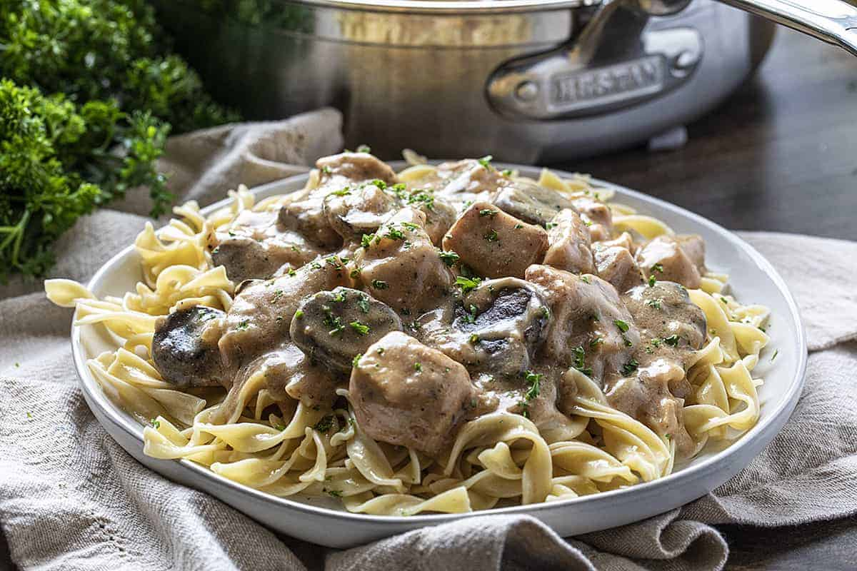 Plate of Chicken Stroganoff next to Skillet and with Parsley