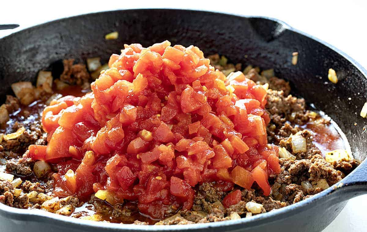 Making Taco Chili, adding tomatoes to meat