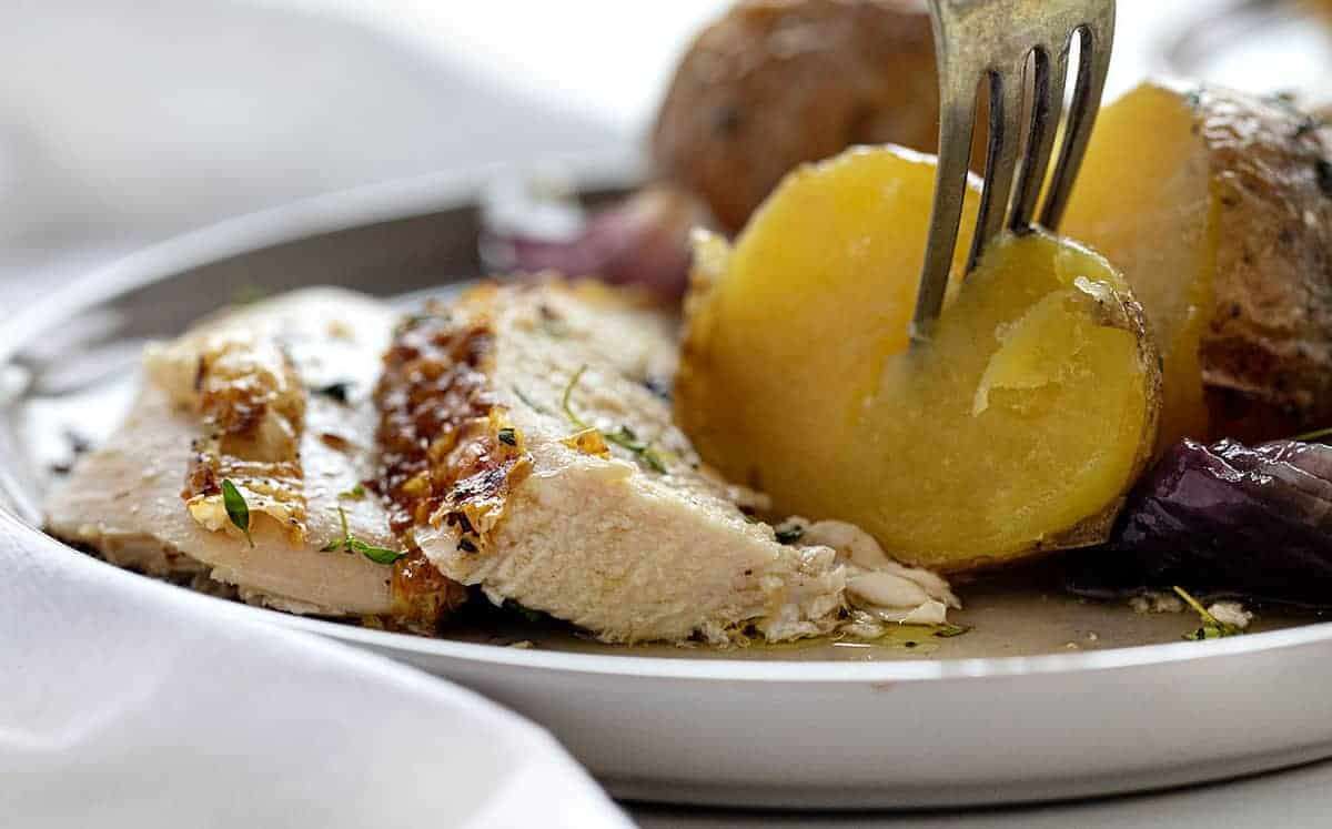 Fork stabbing potato and plated Roasted Chicken