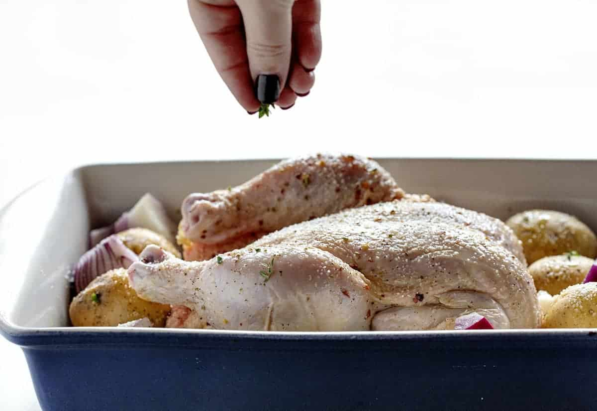 Seasoning raw chicken in a pan