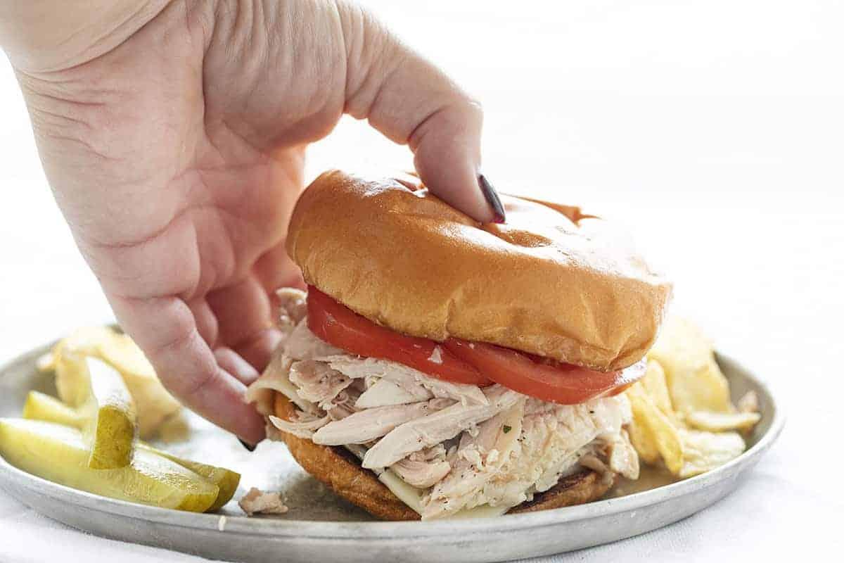 Hand Picking up Rotisserie Chicken Sandwich