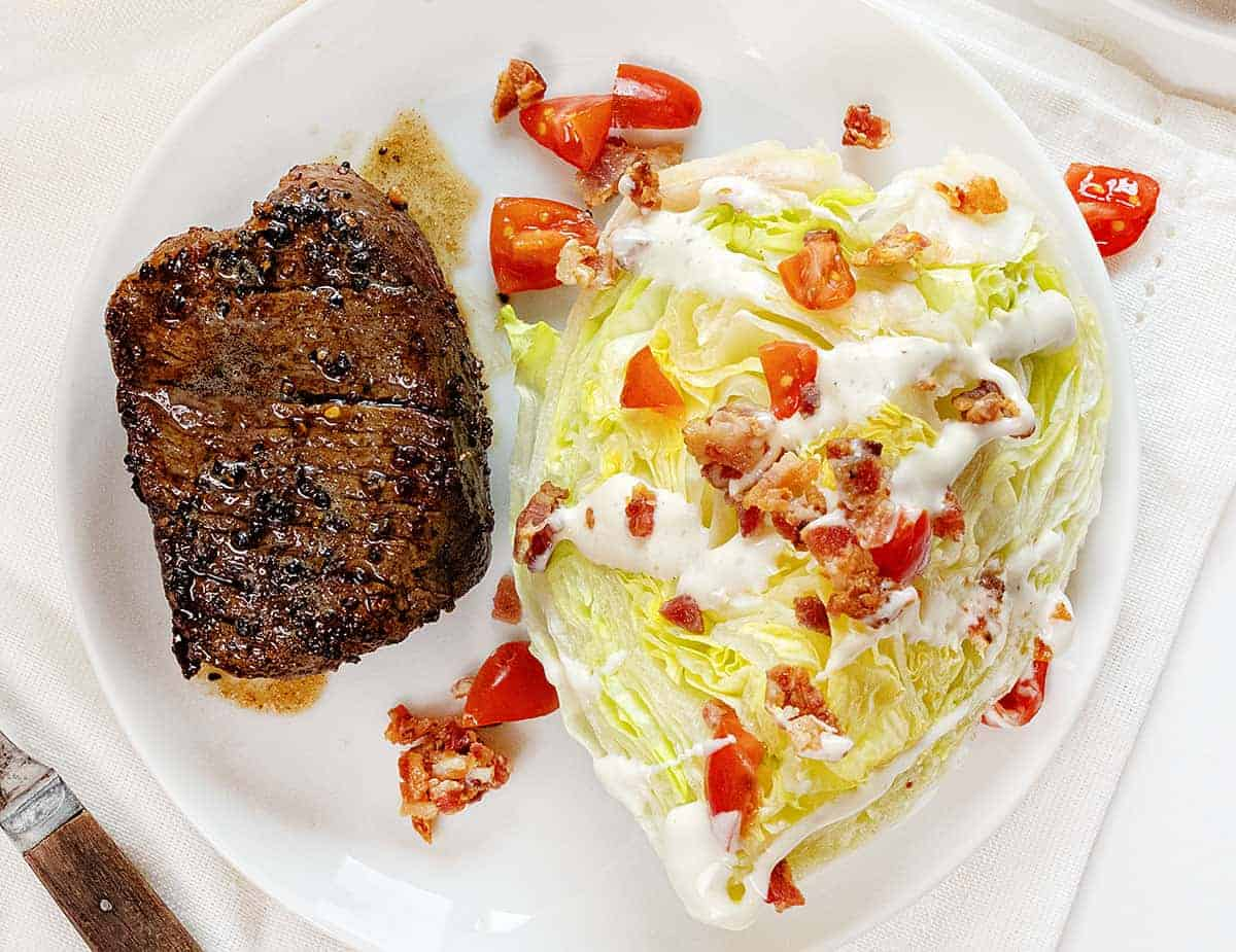 Overhead view of Pepper Crusted Tenderloin on a White Plate with a Wedge Salad