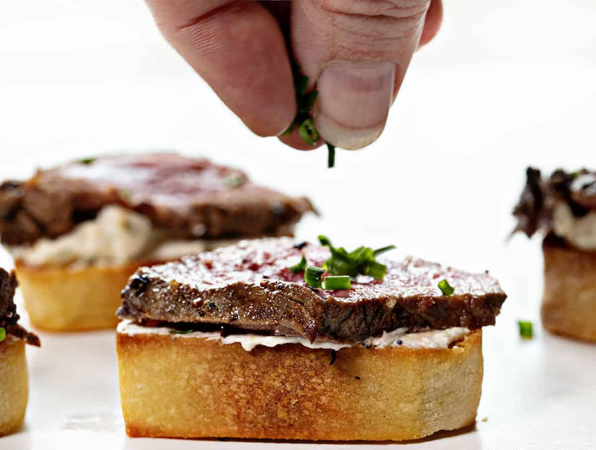 Sprinkling Chives on a Beef Tenderloin Baguette Appetizer