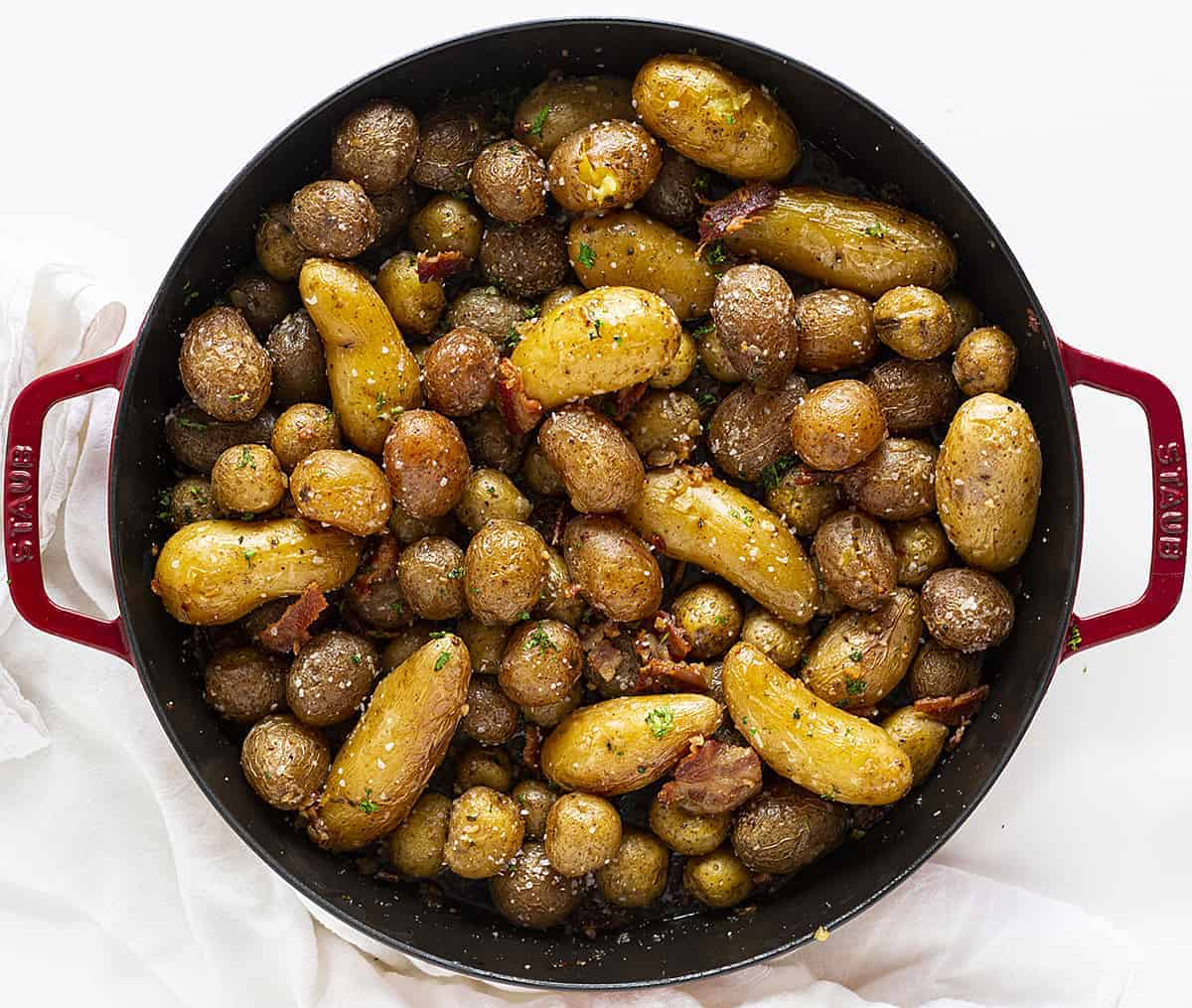 Roasted Potatoes with Bacon OVerhead View in Red Skillet on White Napkin