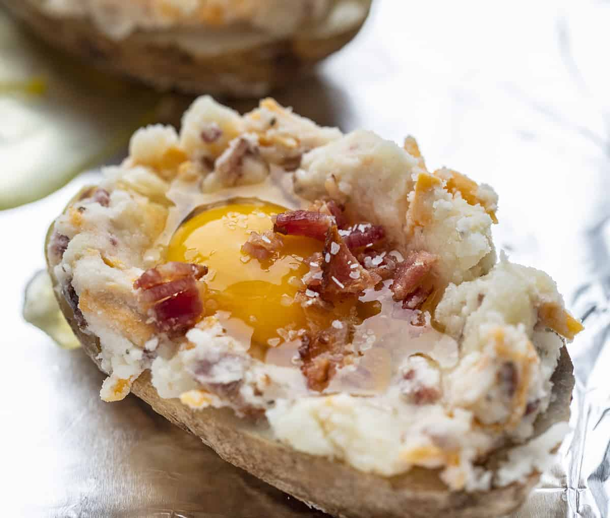 Preparing Twice Baked Potato with Raw Egg and Bacon