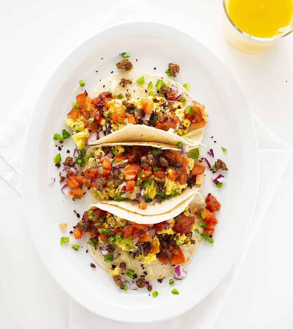 Overhead view of Breakfast Taco Recipe on White Plate with Orange Juice