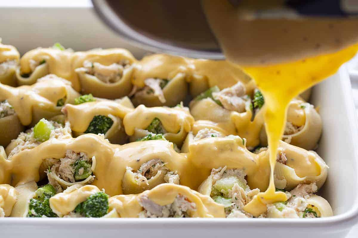 Pouring Cheese Sauce over Chicken Broccoli Stuffed Shells