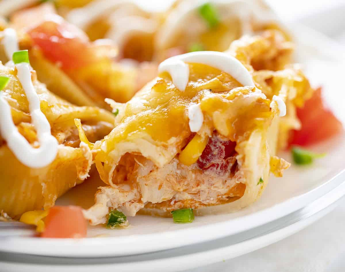 Cut Into Chicken Taco Stuffed Shells on White Plates
