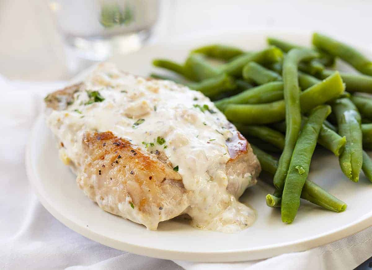 Cream Cheese Pork Chops On White Plate with Green Beans