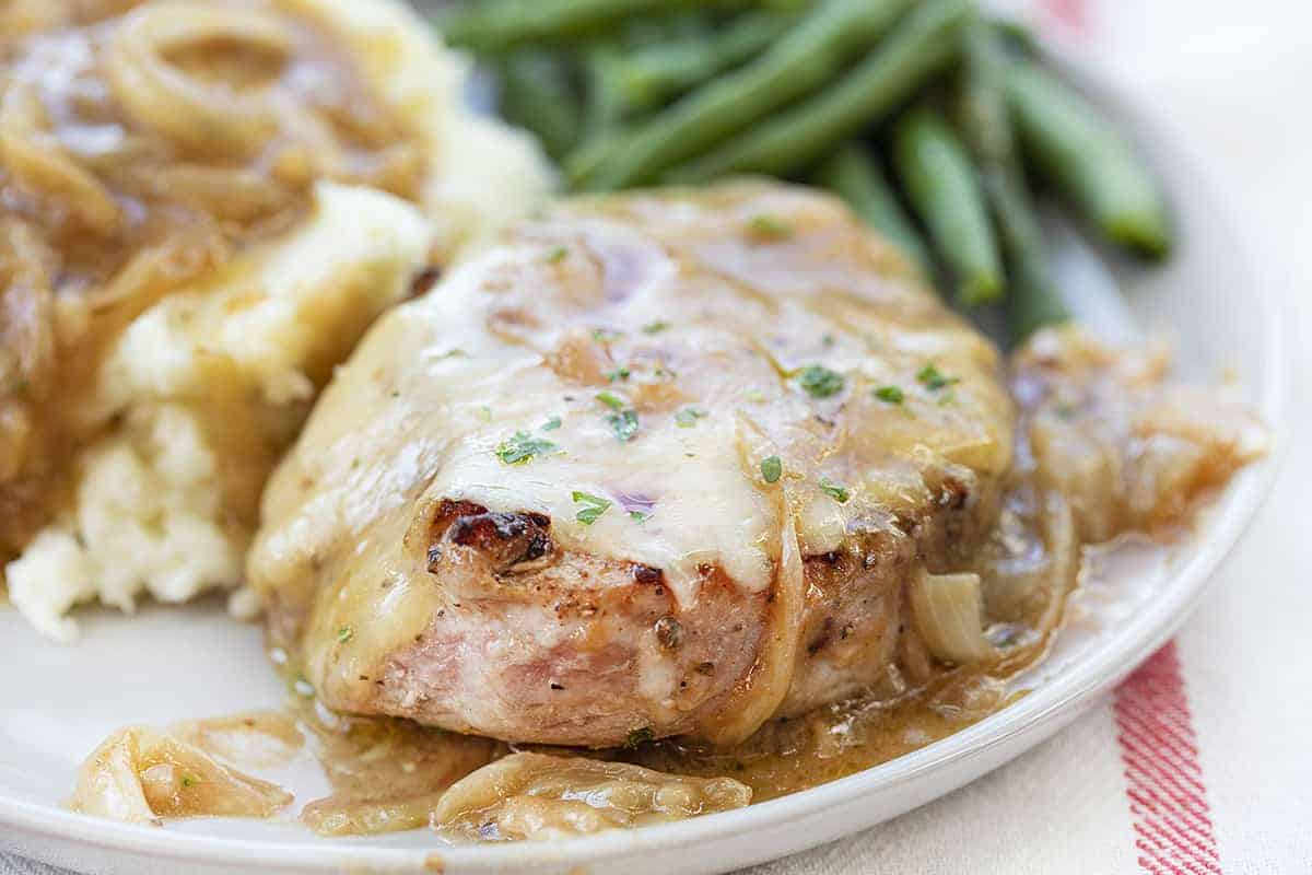 One French Onion Pork Chop on a White Plate with Mashed Potatoes and Green Beans