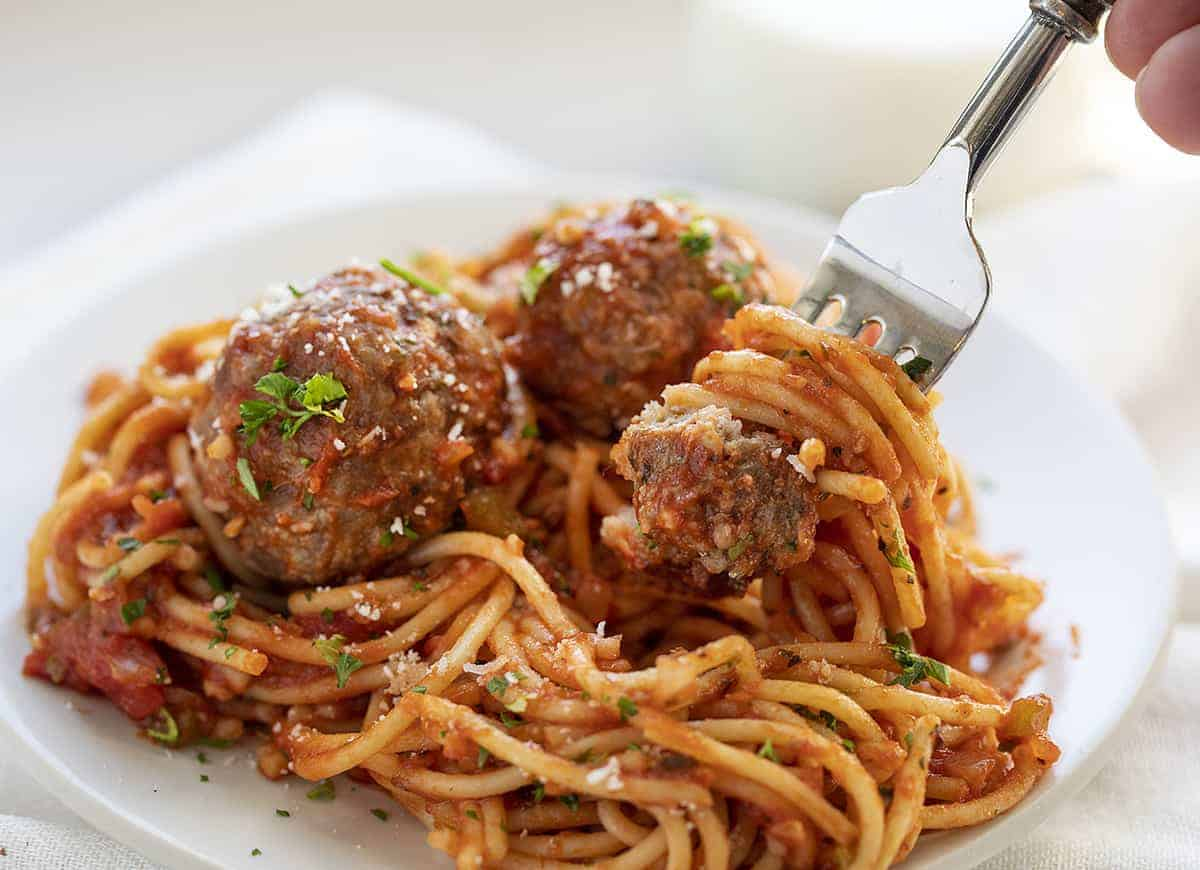 Fork picking up meatball and sauce coated spaghetti noodles