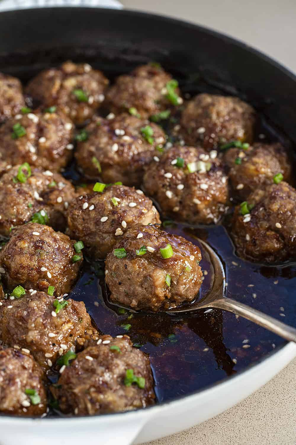 Teriyaki Meatball Recipe in a White Skillet with One on a Spoon