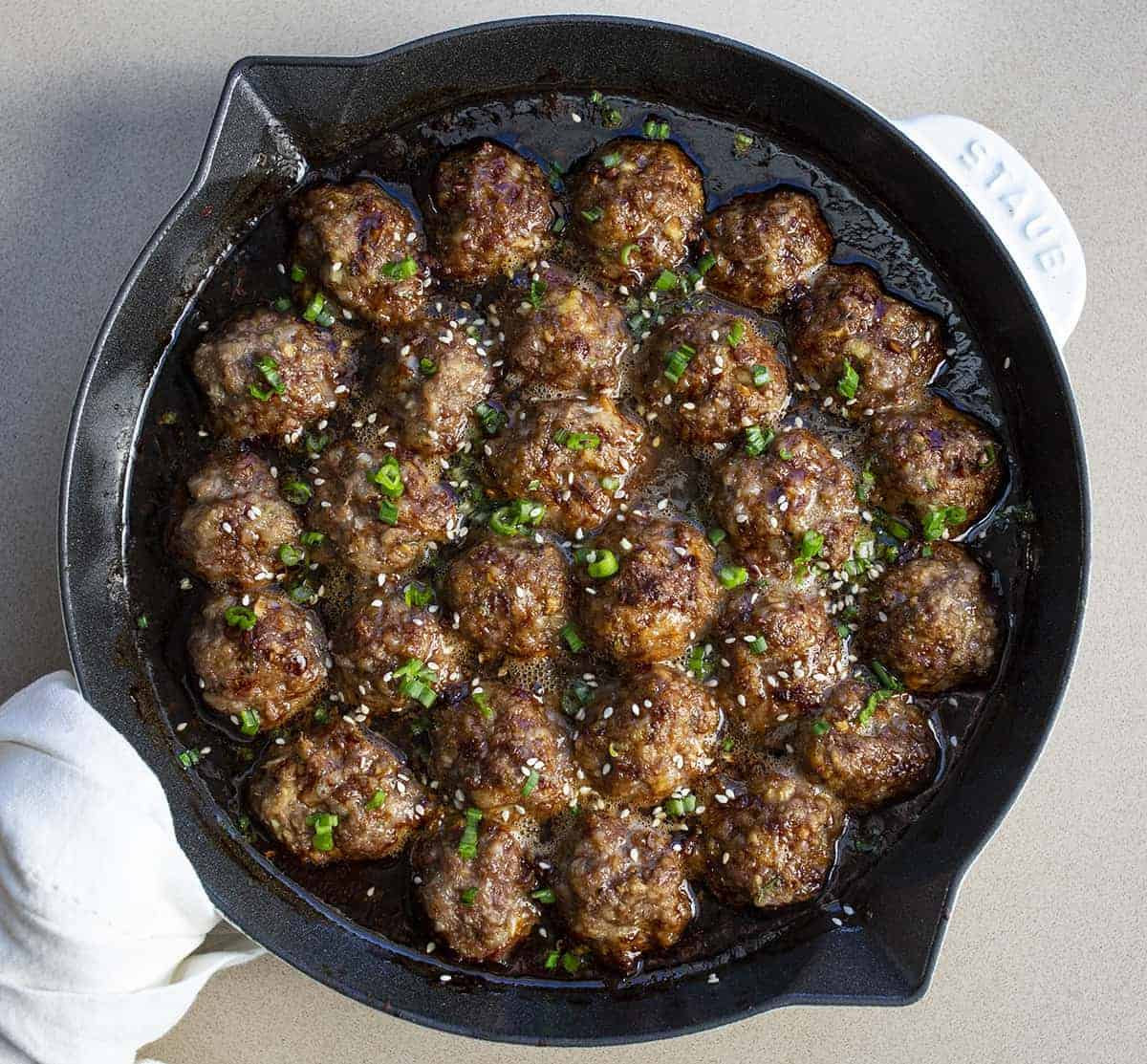 Teriyaki Meatballs in a White Skillet Looking from Overhead