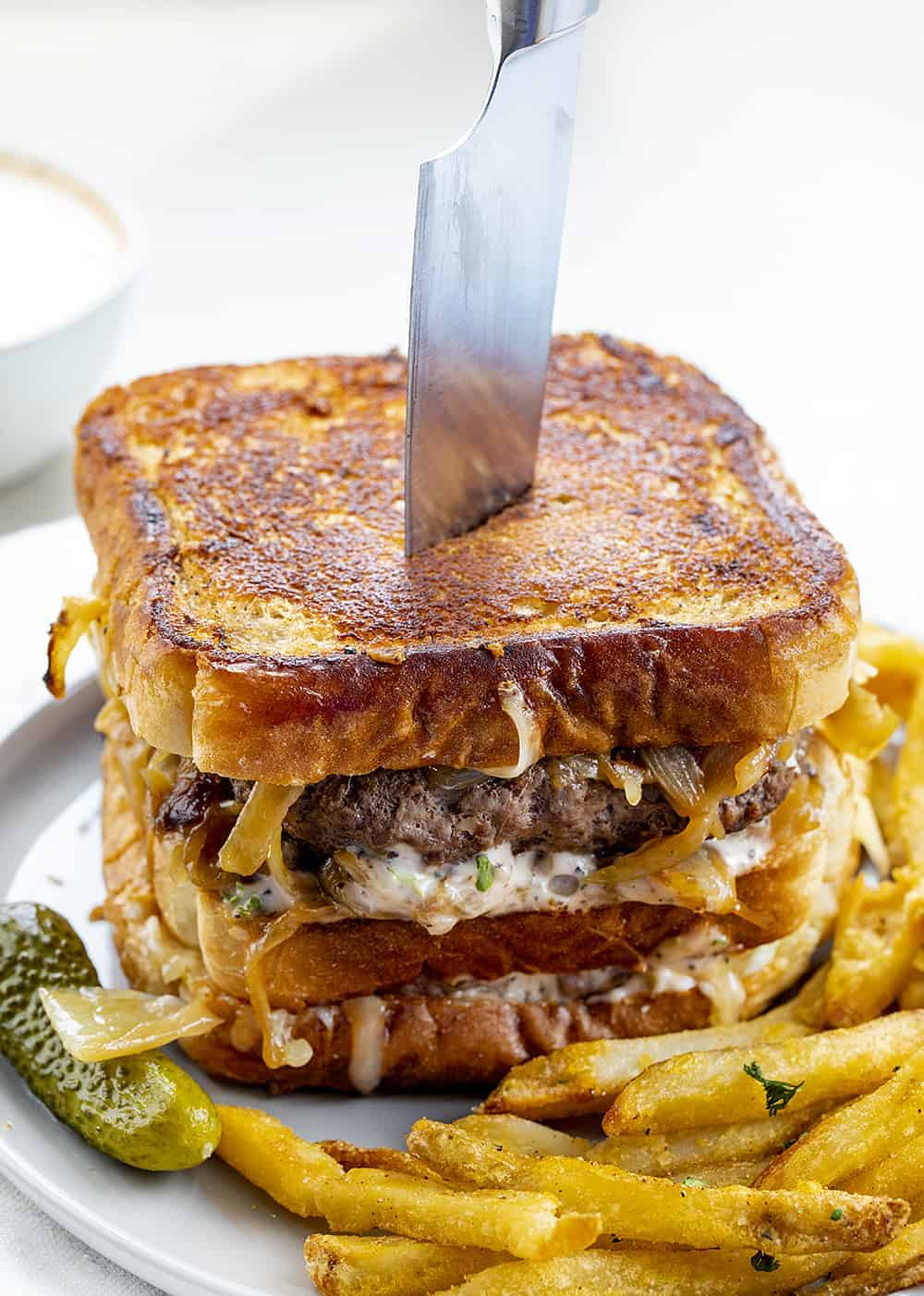 Double Decker Patty Melt Sandwich on a Plate with a Knife in It
