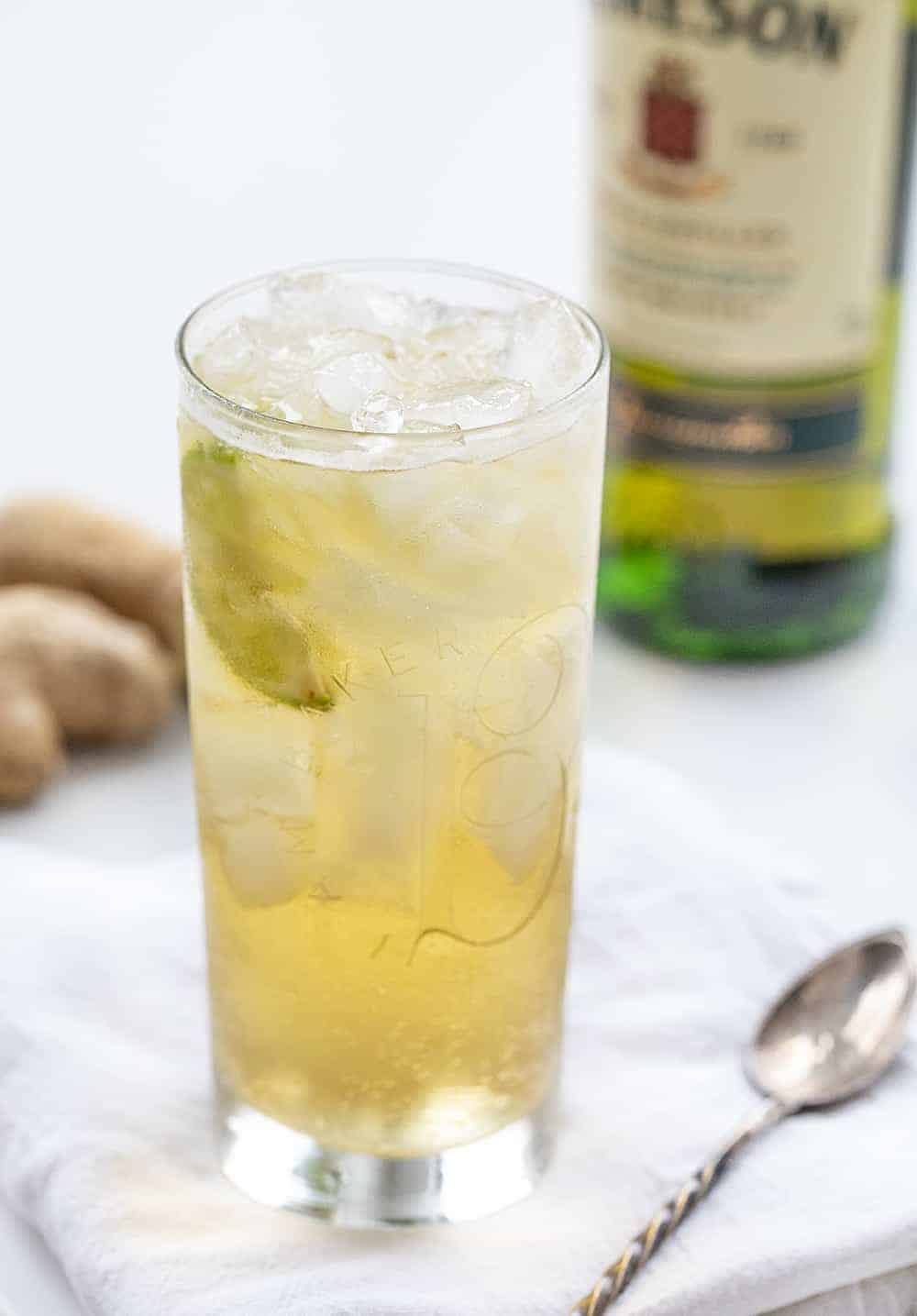 Tall Glass of Jameson Ginger Ale with Lime and Fresh Ginger and Spoon