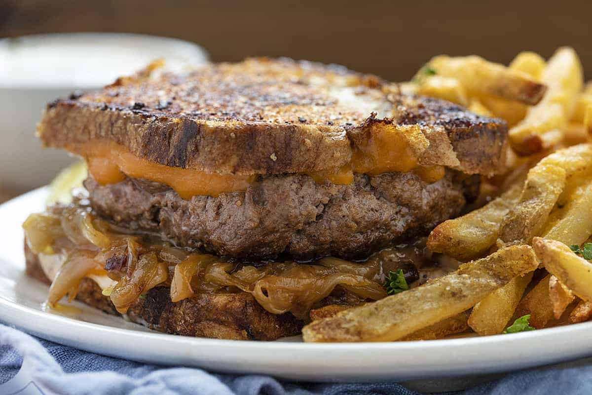 Patty Melt Sandwich on a White Plate with French Fries