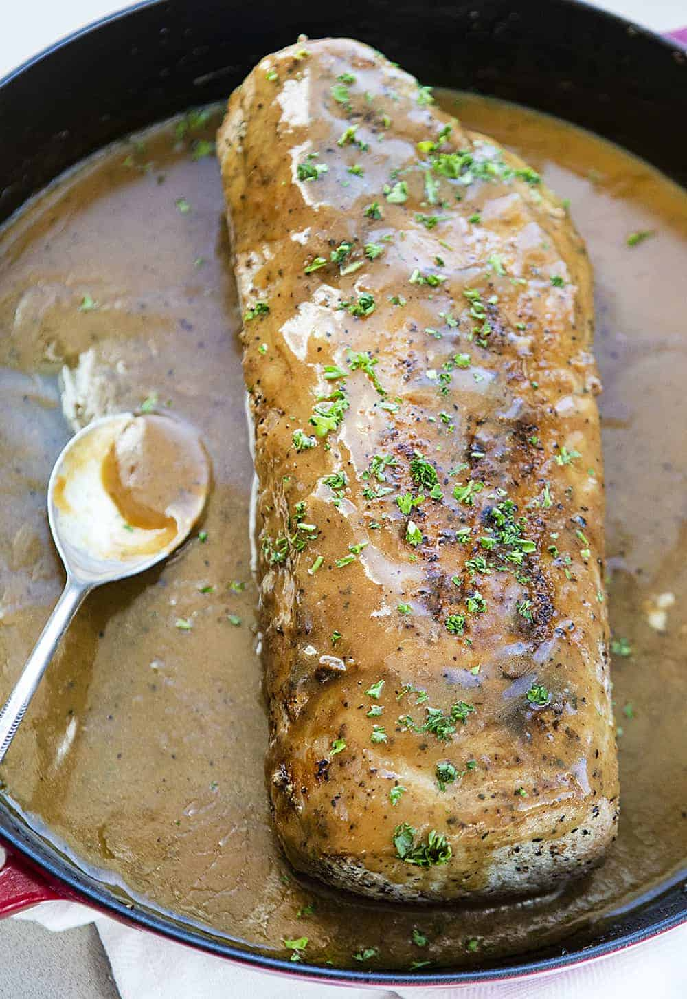 Roasted Pork Loin with Gravy in a Skillet with Spoon