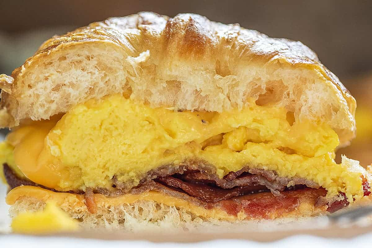 Bacon Egg and Cheese Croissant Cut in Half and Exposing Inside of Sandwich