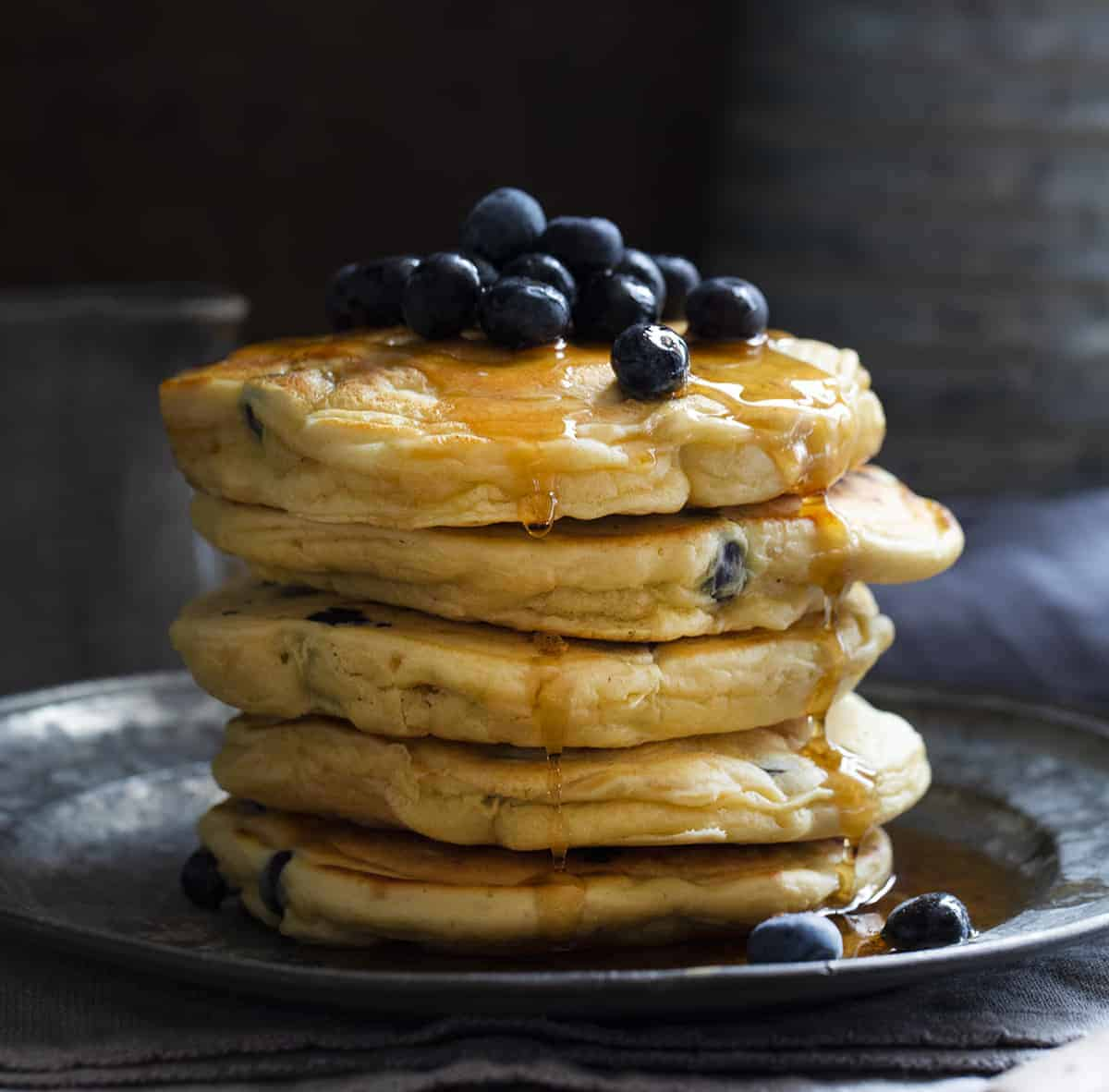 Blueberry Sourdough Pancakes Stacked on Plate with Blueberries
