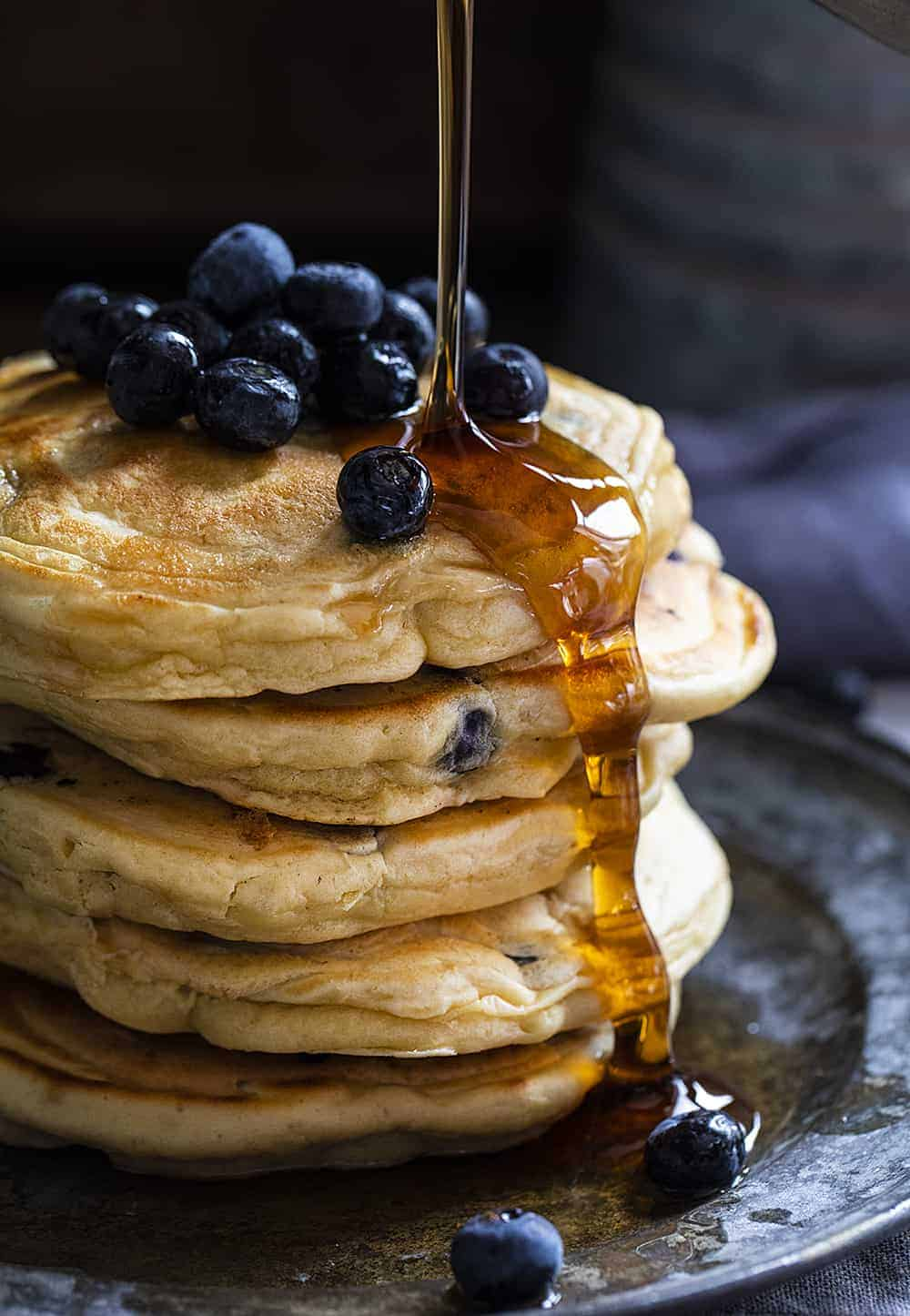 Pouring Syrup over Blueberry Sourdough Pancakes with Fresh Blueberries
