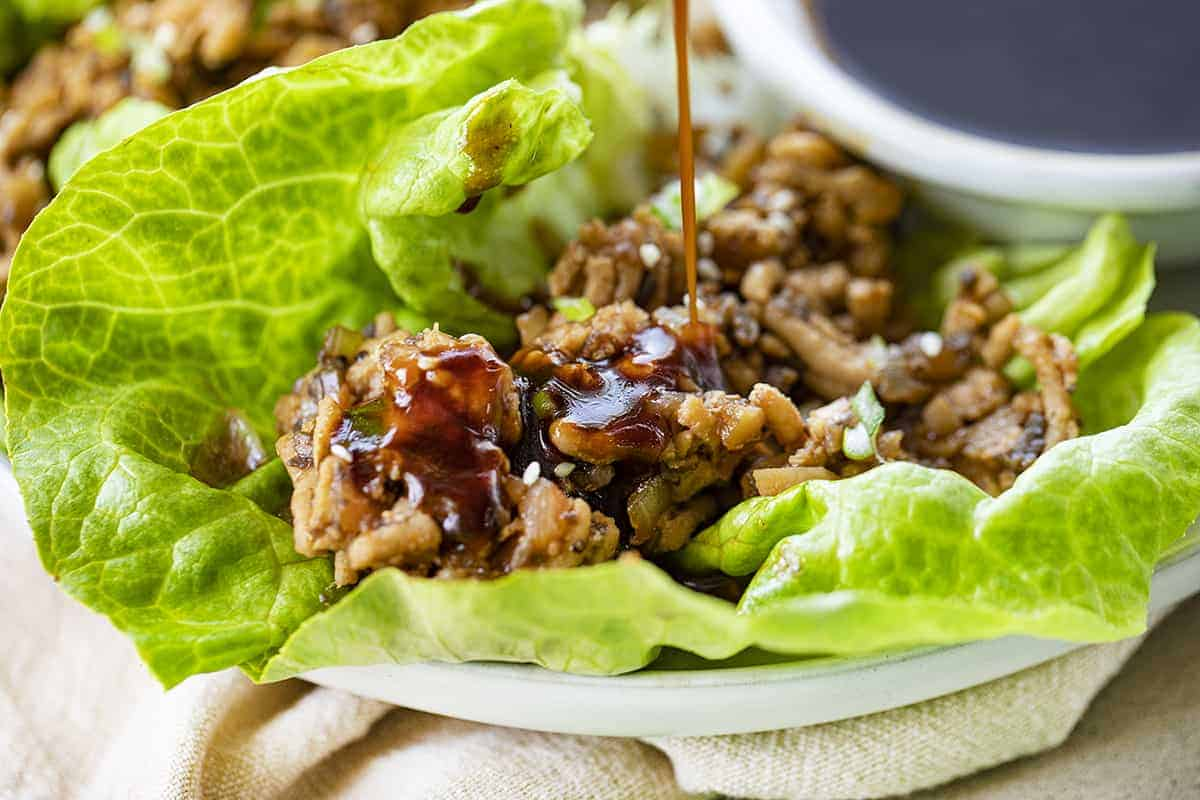 Pouring Sauce over Chicken Lettuce Wraps on White Plate