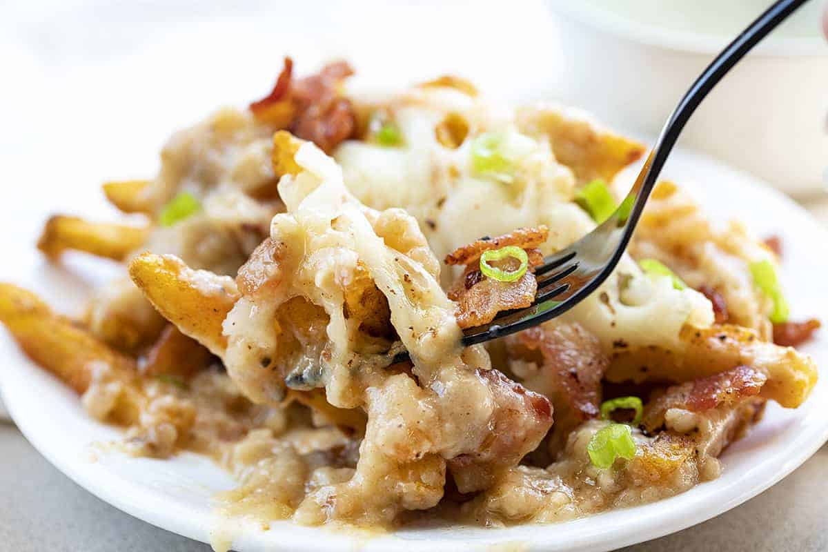Plate of Poutine Soaked in Gravy and Fork Picking Up a Bite