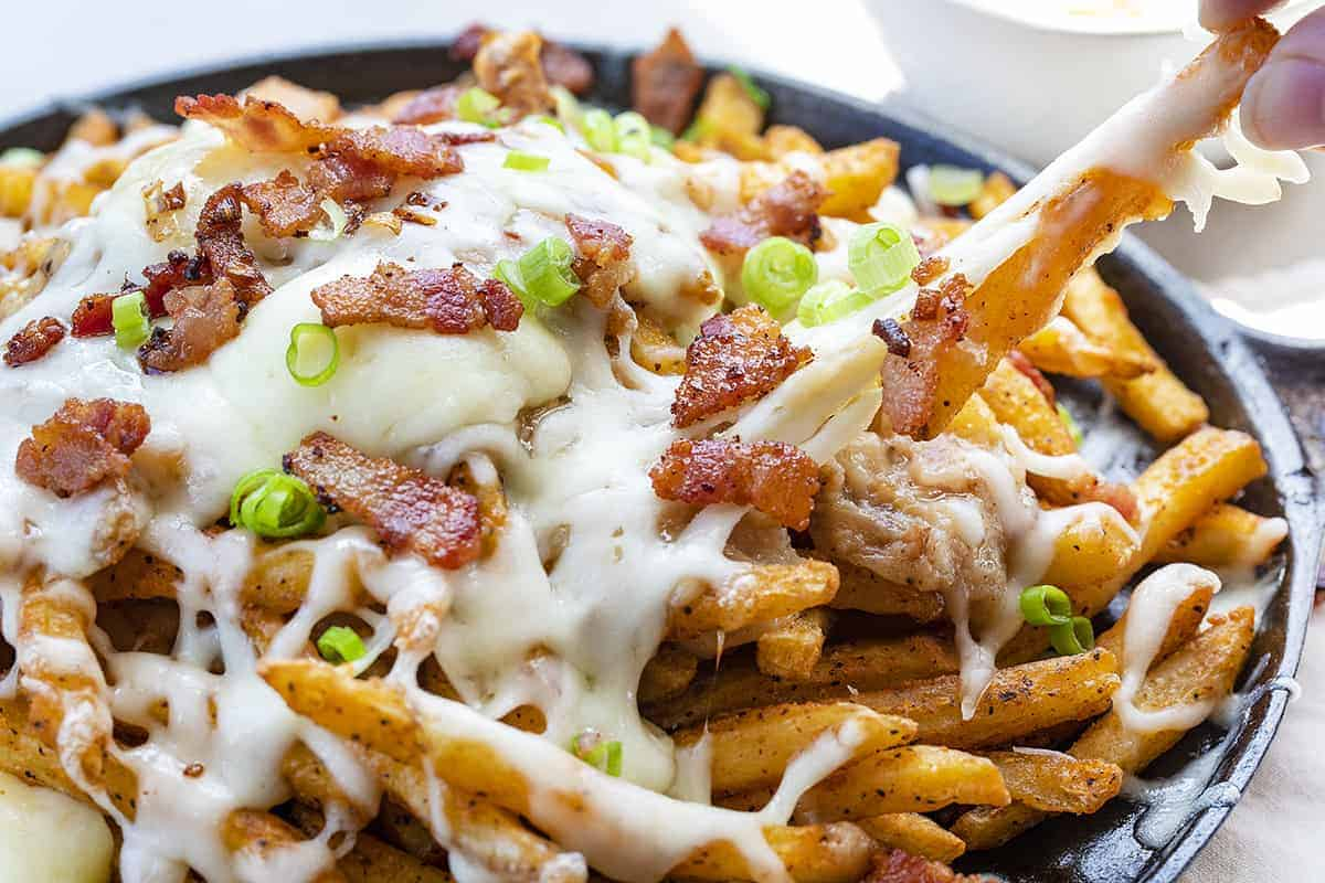 Pulling a French Fry from a Poutine Skillet Cheese is Stretching