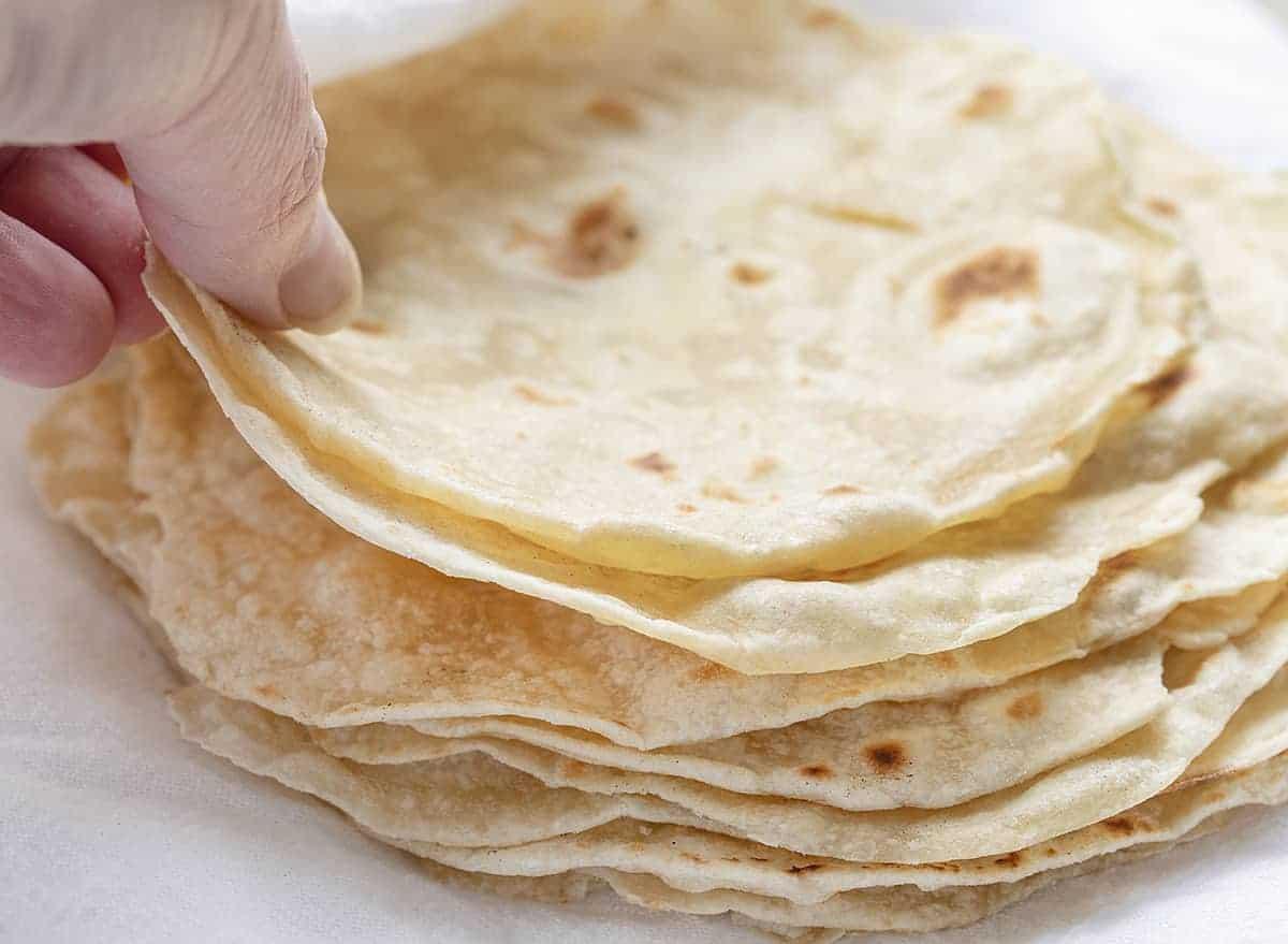 Hand Picking Up Homemade Tortillas