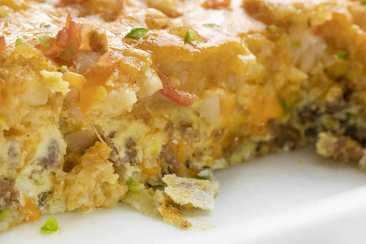 Close up of Breakfast Tater Tot Casserole in a White Pan with Egg and Cheese