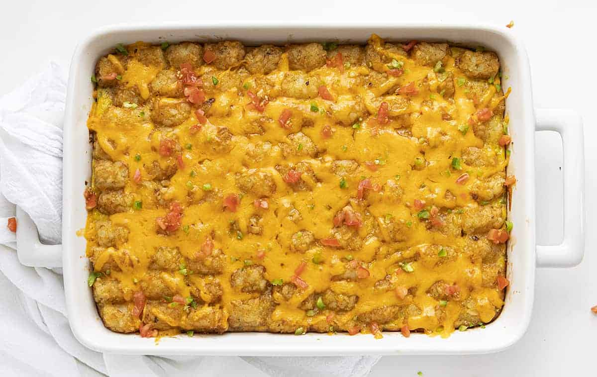 Breakfast Tater Tot Casserole Shot from Overhead in a White Casserole Dish on White Surface