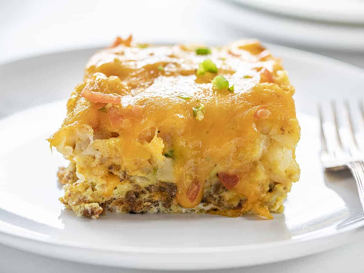 Breakfast Tater Tot Casserole With Cheesy Oozing Down on a White Plate with White Fork