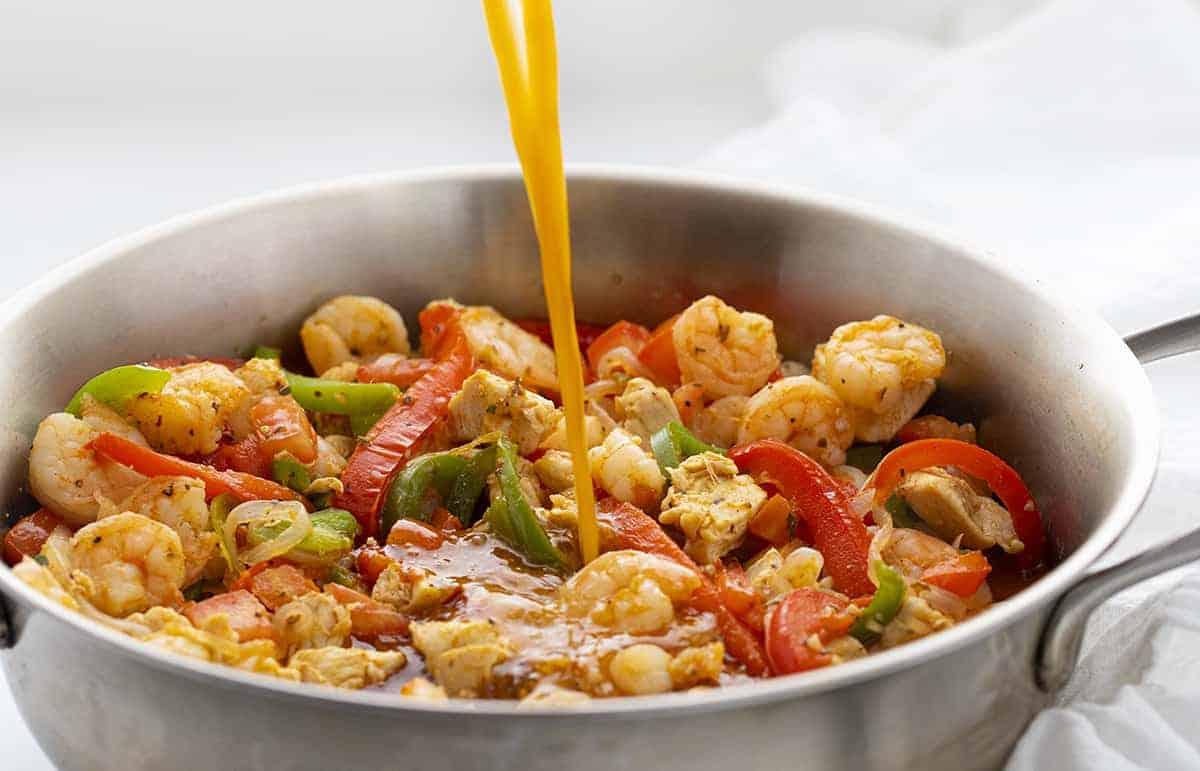 Pouring Sauce into Cajun Chicken Jumbalaya Pasta
