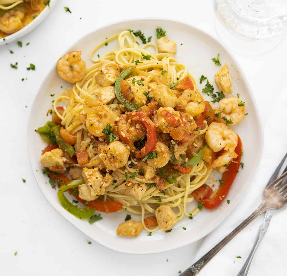 Overhead View of Cajun Chicken Jumbalaya Pasta on White Plate with Forks and White Napkin