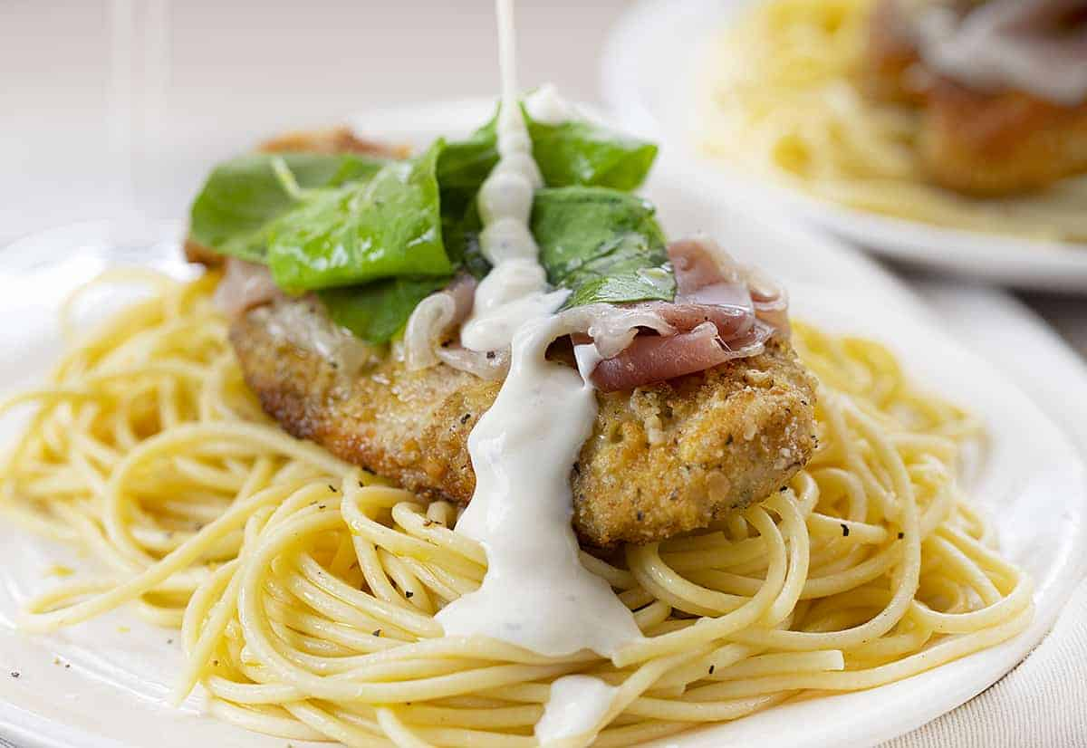 Drizzling Parmesan Sauce over Chicken and Spaghetti Noodles to Make Cheesecake Factory Chicken Bellagio Recipe