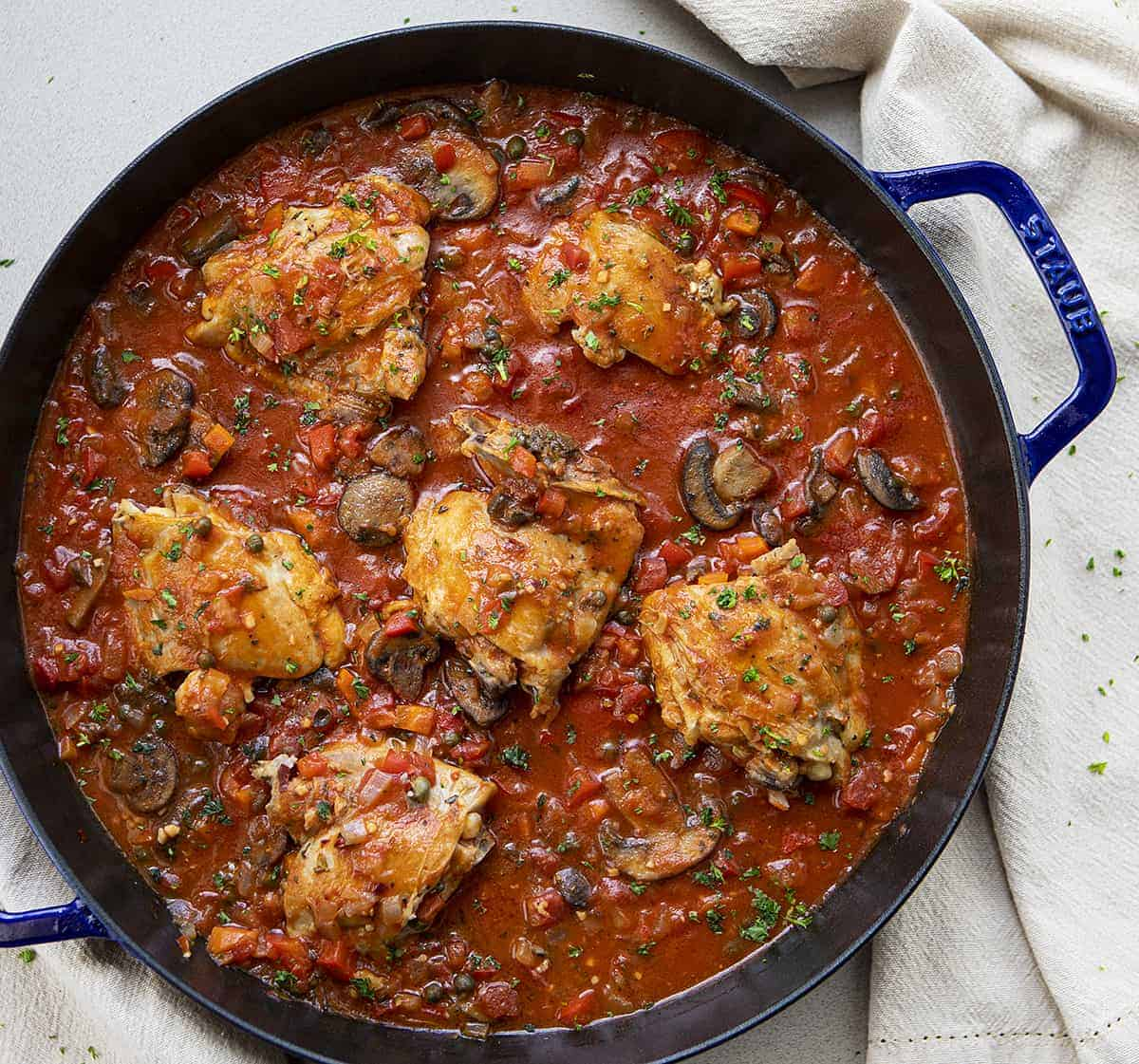 Overhead Image of Cheesecake Factory Chicken Cacciatore in a Blue Skillet with Towels Next to Skillet