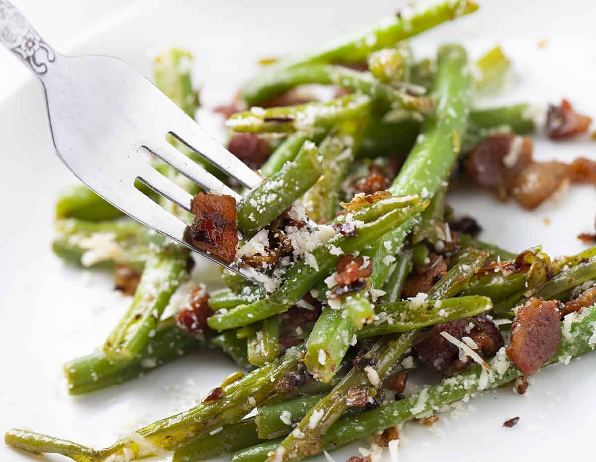 Forkful of Spicy Green Beans with Bacon and Cheese on White Plate