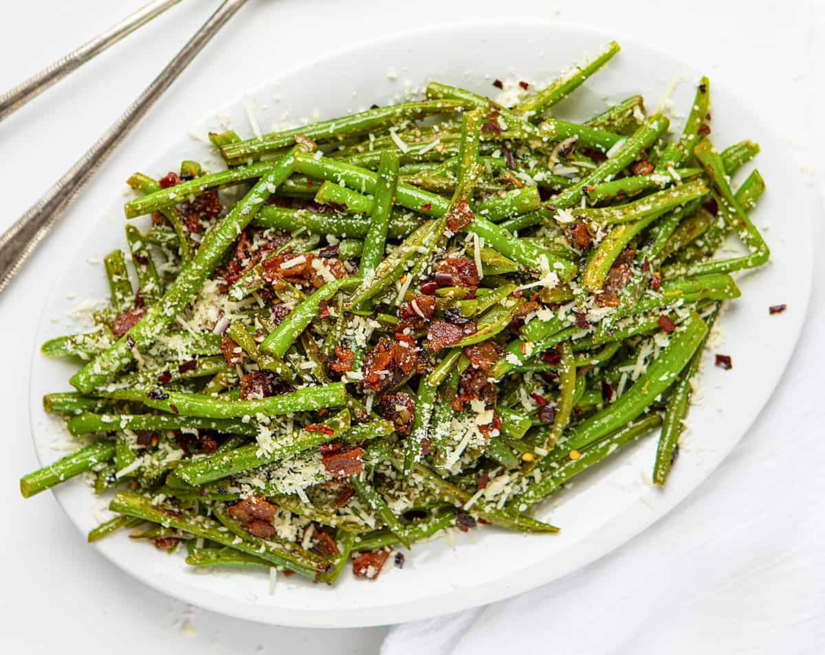 Spicy Green Beans with Bacon Recipe on White Plate with Spoons Next to It