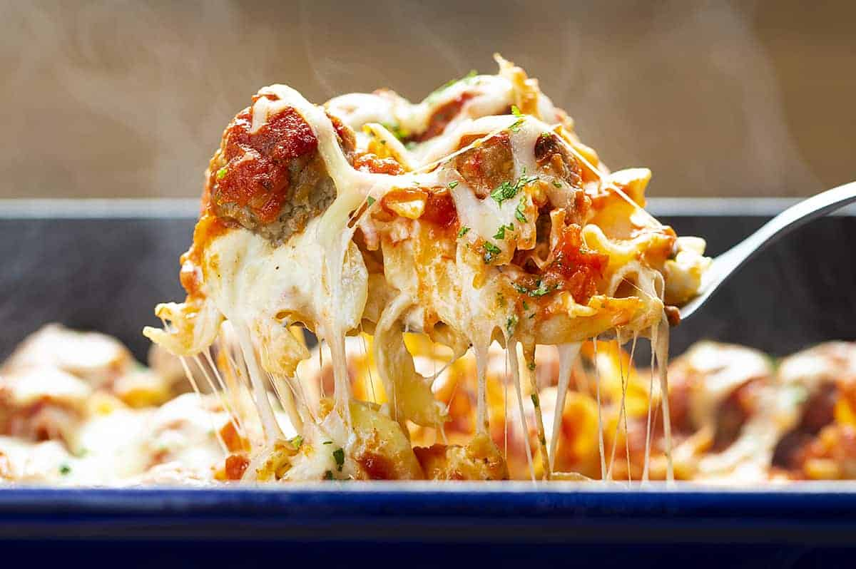 Spatula Picking Up Cheesy Meatball Casserole from Blue 9x13 Pan