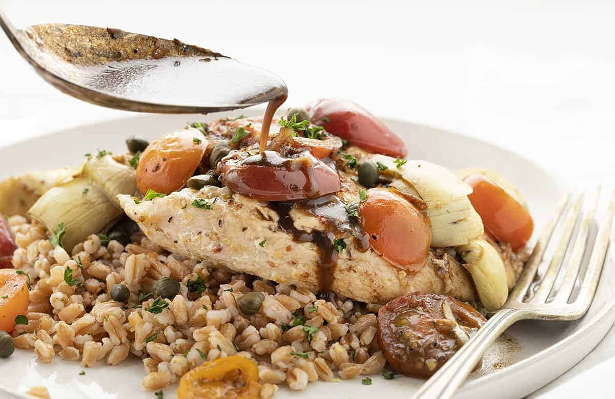 Drizzling Balsamic Glaze over Tuscan Chicken on White Plate Copycat Cheesecake Factory