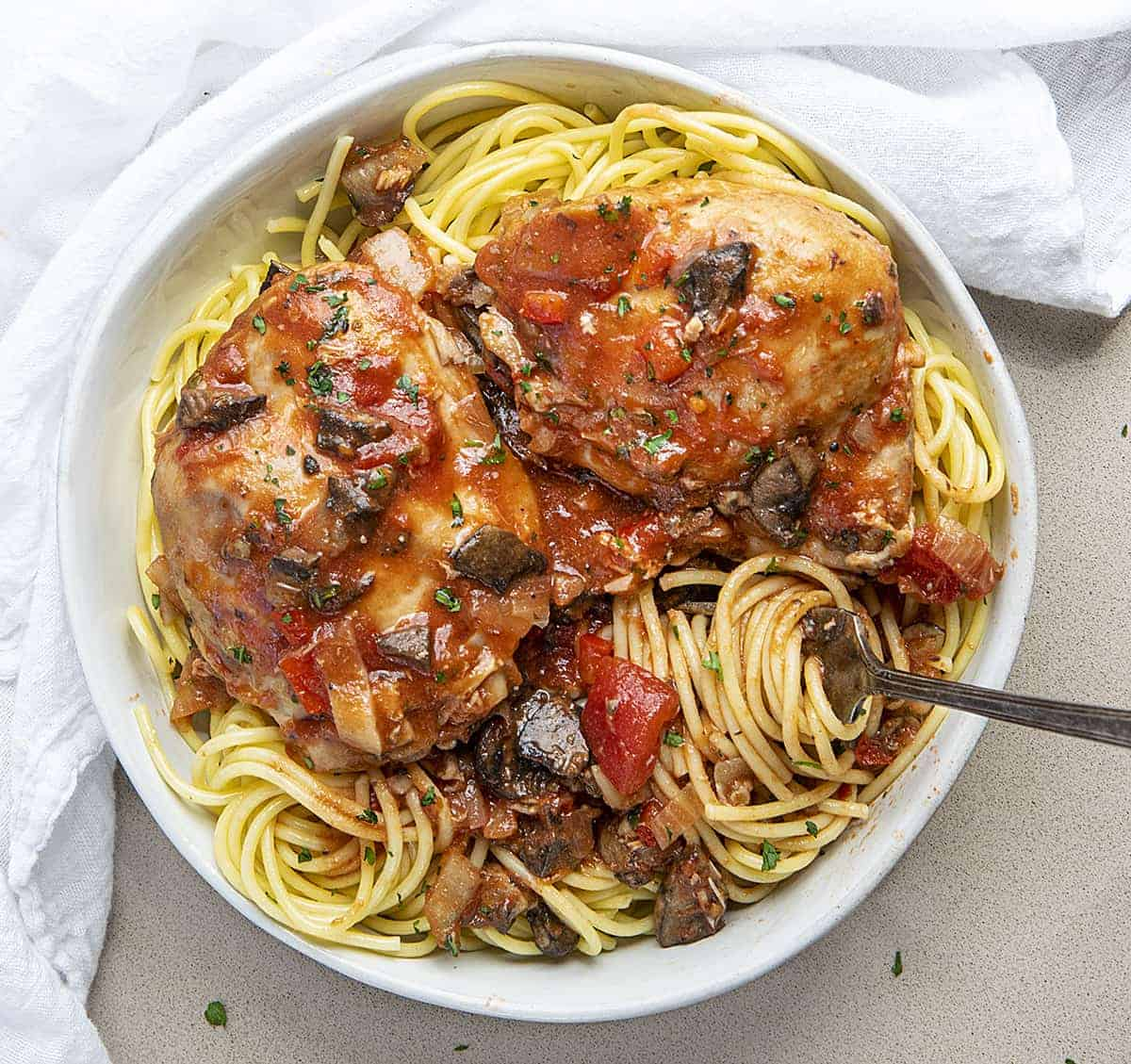 Overhead view of a White Bowl of Slow Cooker Chicken Cacciatore with Fork