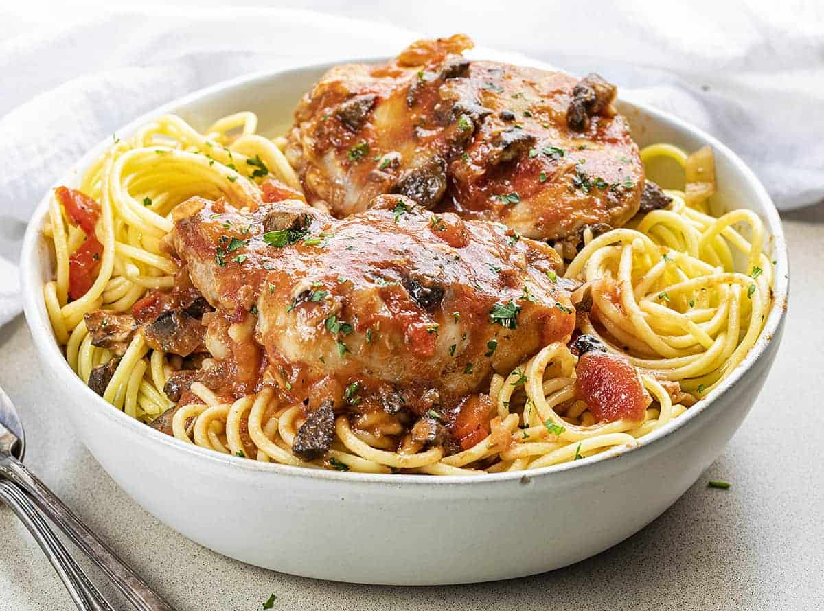 White Bowl Filled with Slow Cooker Chicken Cacciatore over Spaghetti Noodles