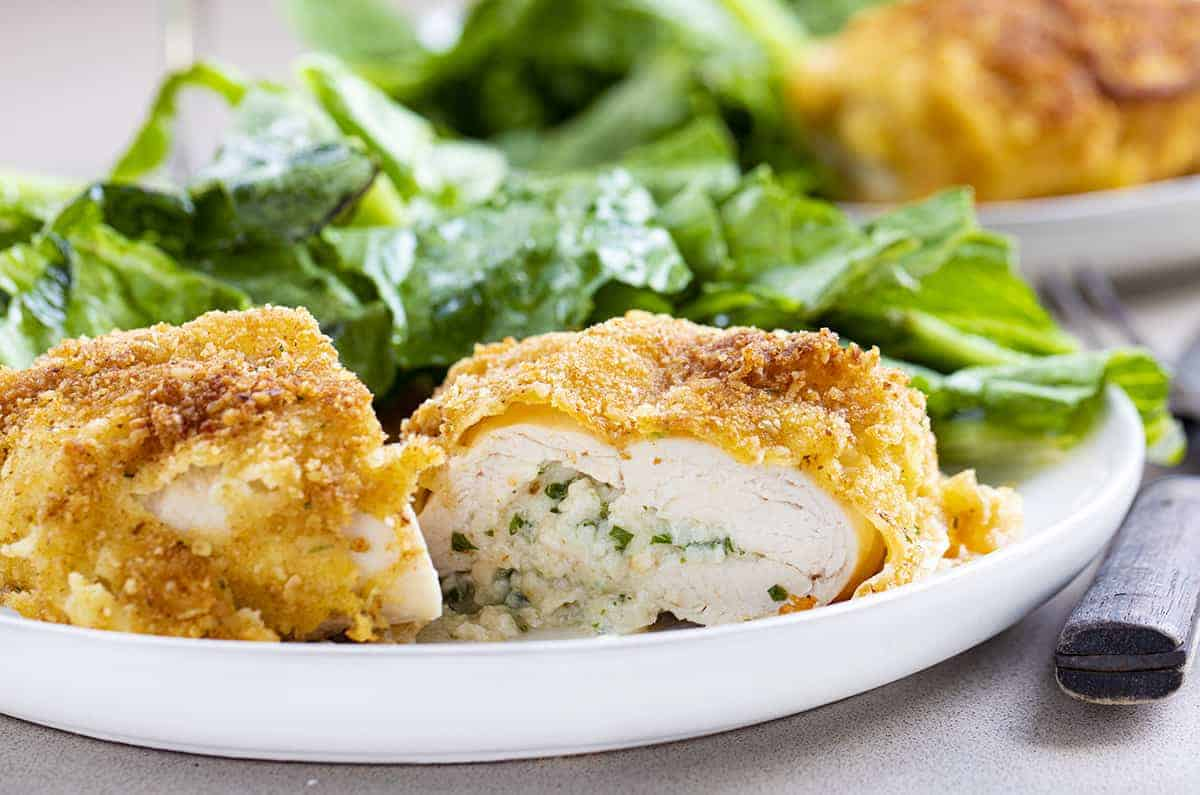 Cut Into Chicken Kiev on a Plate with Greens