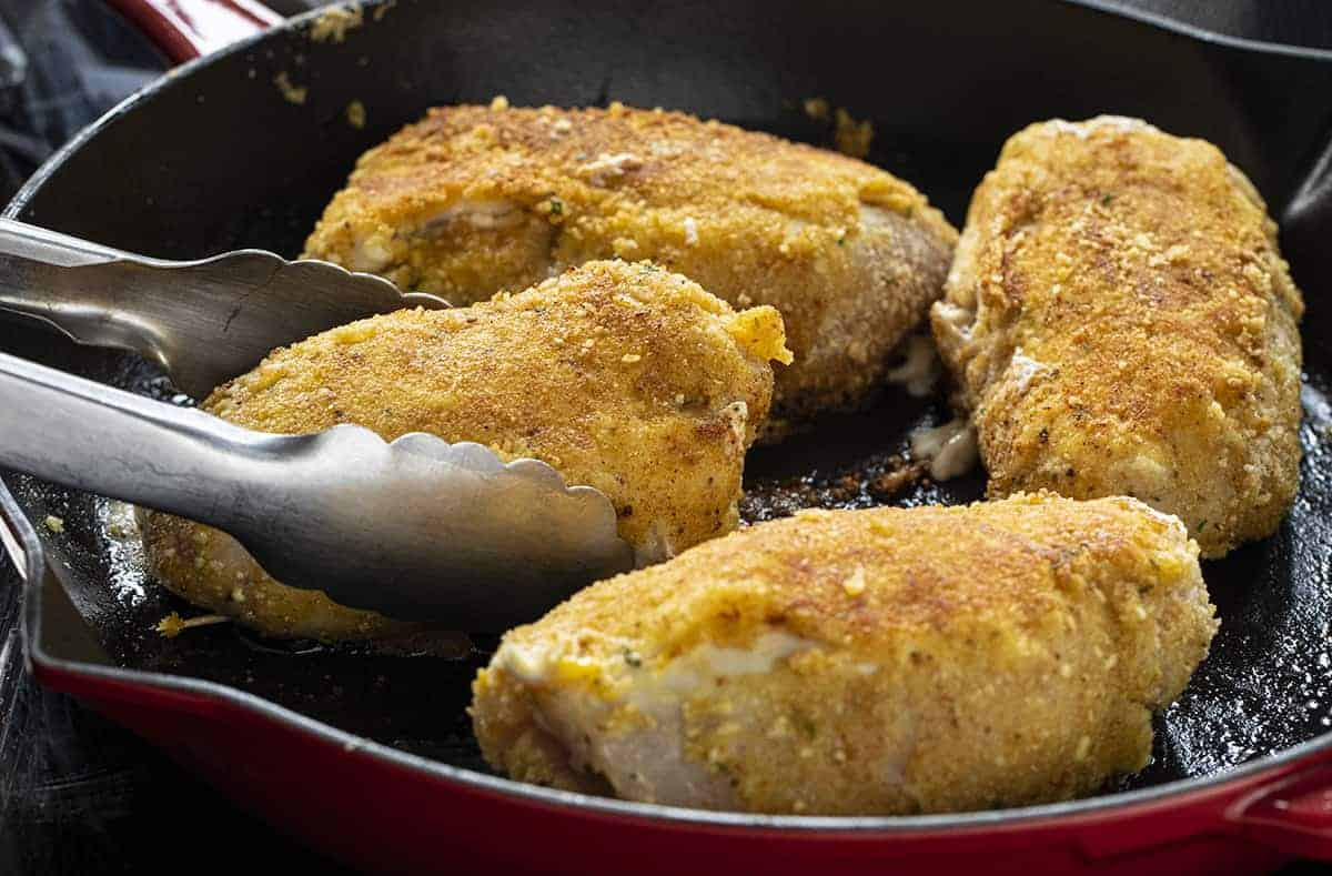 Frying Chicken Kiev in a Red Pan and Using a Tongs to Flip