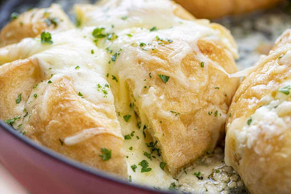 Cheesy Garlic Pull Apart Bread Very Close Showing Gooey Cheese in a Red Skillet