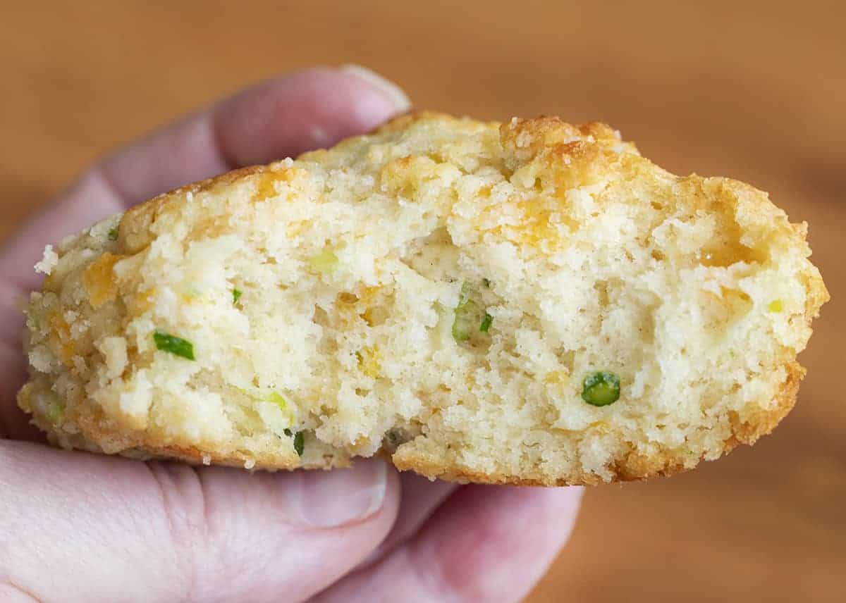 Hand Holding Cheesy Garlic Scapes Biscuit over Wood Cutting Board