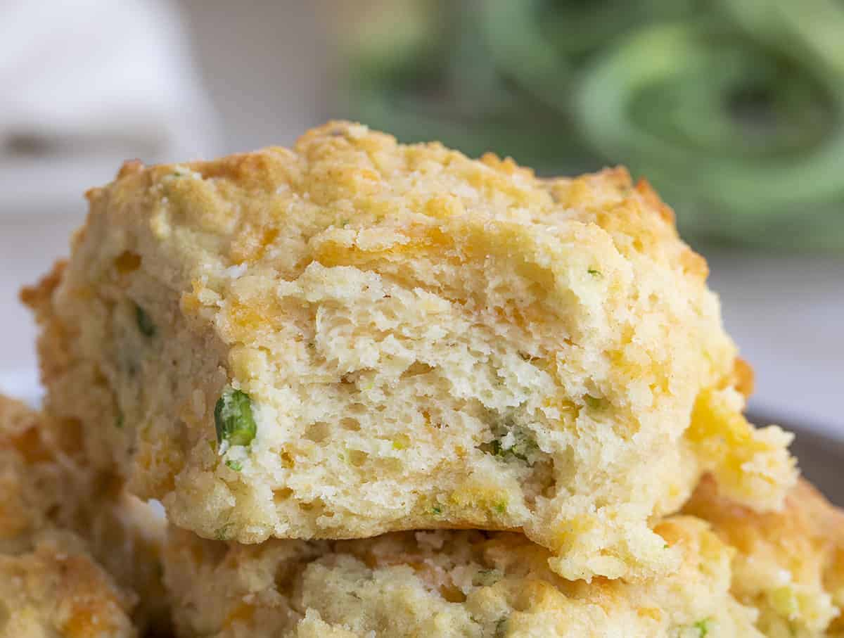 Close Up of the Inside of a Cheesy Garlic Scapes Biscuit with Garlic Scapes in Background
