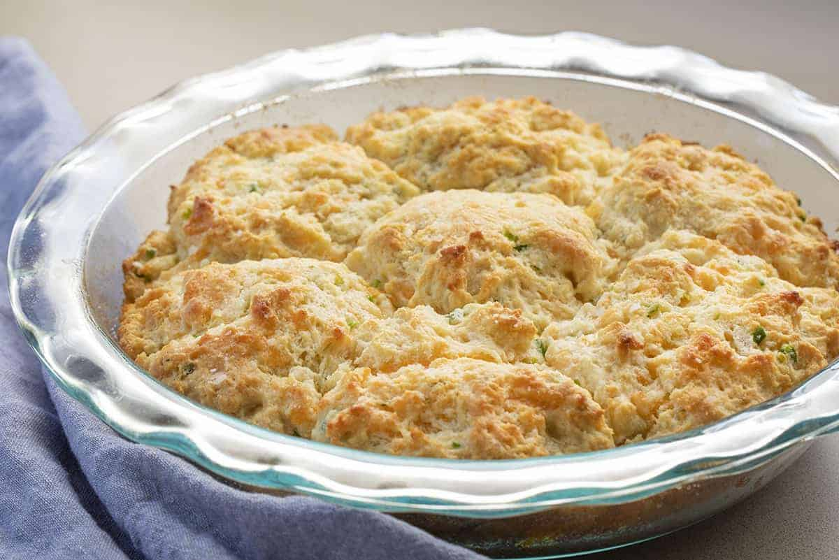 Glass Baking Dish with Baked Cheesy Garlic Scapes Biscuits and Blue Towel Next to It